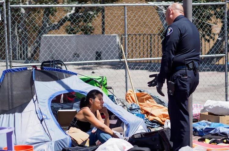 Un efectivo de la Policía le dice a Michele Salcedo (i) que deje su tienda en un campamento de personas sin hogar.(EFE).