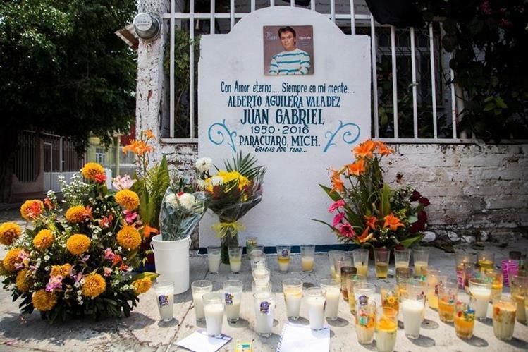 Las velas y las flores se ven en un altar en Parácuaro, Michoacán, México, lugar donde nació Juan Gabriel. (Foto Prensa Libre: AFP)