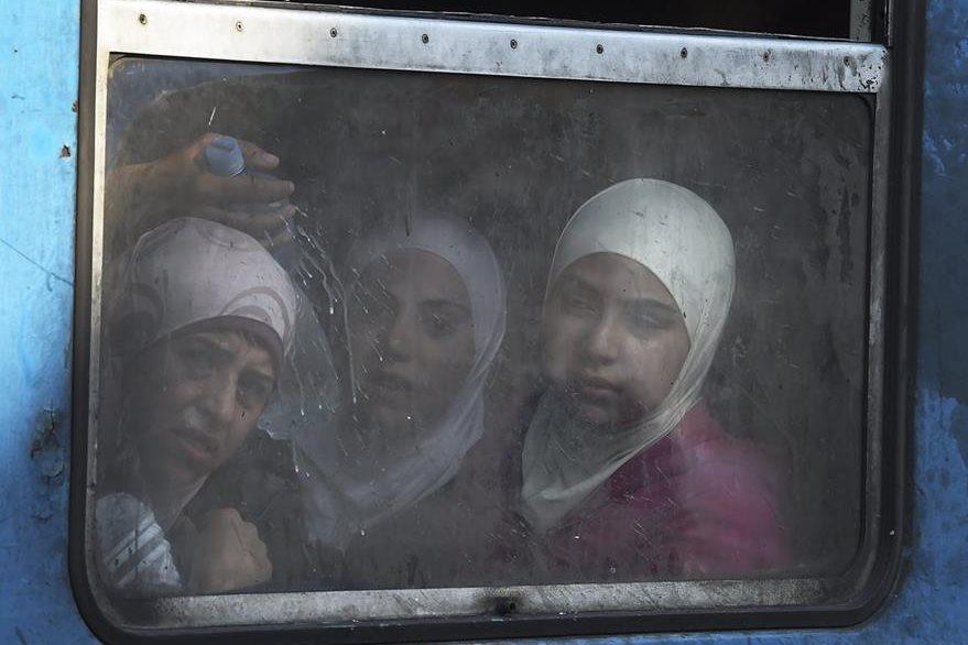Tres mujeres llegadas de Afganistán, miran por la ventana de un tren con destino a Serbia en la estación de Gevgelija, Macedonia. (Foto Prensa Libre: EFE).