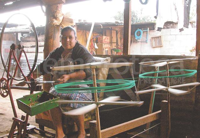 Rosenda Pangán maniobra un chasís de bicicleta invertido, al que se le adaptan dos aros el cual es utilizado para separar los hilos de colores usados en la elaboración de figuras. (Foto: Hemeroteca PL)