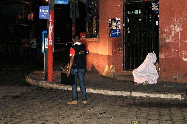 Los cuerpos de dos supuestos extorsionistas cayeron a la banqueta luego de haber sido atacados a balazos en la zona 3 de Escuintla. (Foto Prensa Libre: Carlos Enrique Paredes)
