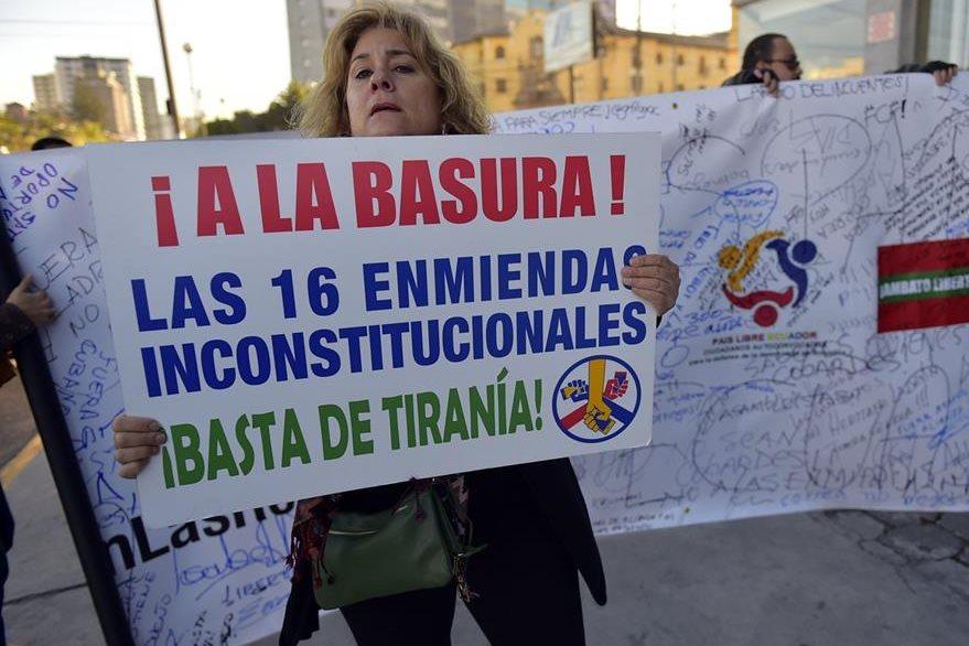 Una mujer sostiene una pancarta durante los enfrentamientos de este jueves. (Foto Prensa Libre: AFP).