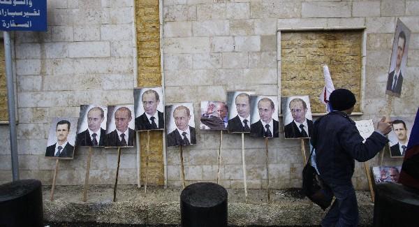 Un partidario del presidente Bachar al Asad prepara fotos del mandatario antes salir amanifestar.