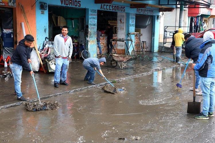 Comerciantes de Xelajú retiran el lodo que arrastró la correntada hacia sus locales en la 6ª avenida de la zona 2. (Foto Prensa Libre: Carlos Ventura)