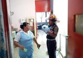 El bombero Wilfredo Morales entrega a una enfermera la bebé rescatada en San Andrés Villa Seca, Retalhuleu. (Foto Prensa Libre: Rolando Miranda)