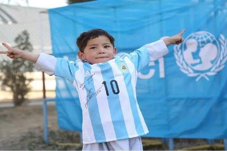 Murtaza Ahmadi, niño afgano posa con una de las camisetas firmadas por Lionel Messi.
