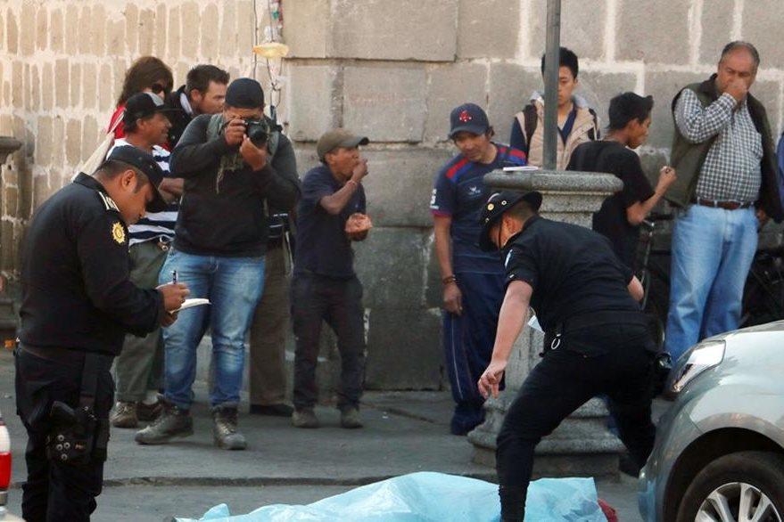 Curiosos observan el lugar donde murió baleado Rodolfo Reyes. (Foto Prensa Libre: Carlos Ventura).