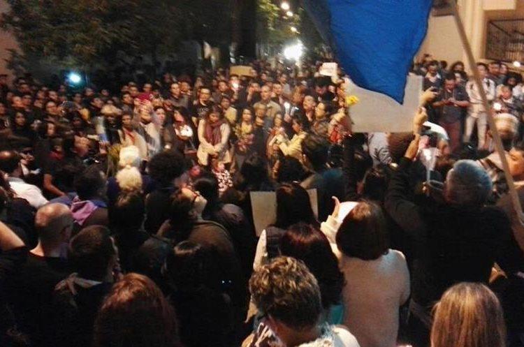 Una bandera con una listón negro se alza sobre la manifestación