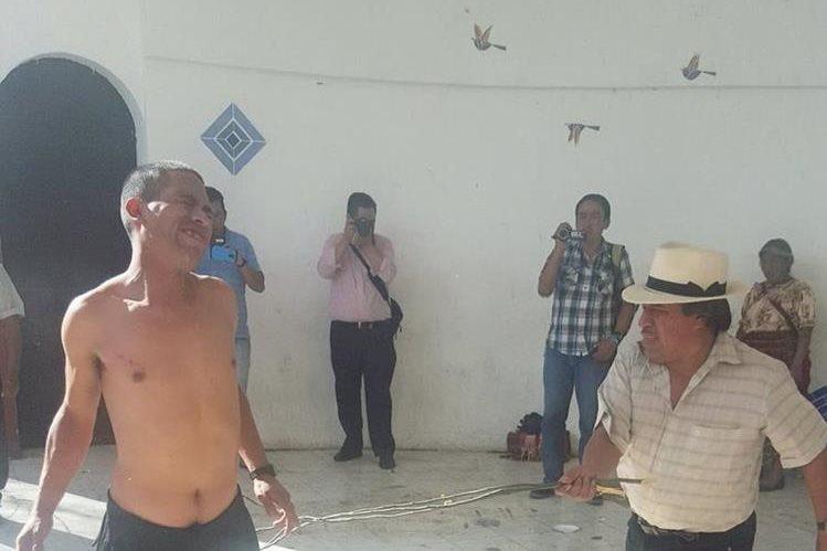 Uno de los dos señalados recibe el castigo maya por parte de la autoridad comunitaria. (Foto Prensa Libre: Knal 4)