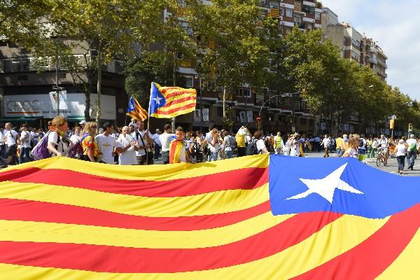 Manifestantes despliegan una gran bandera catalán independentista en Barcelona.