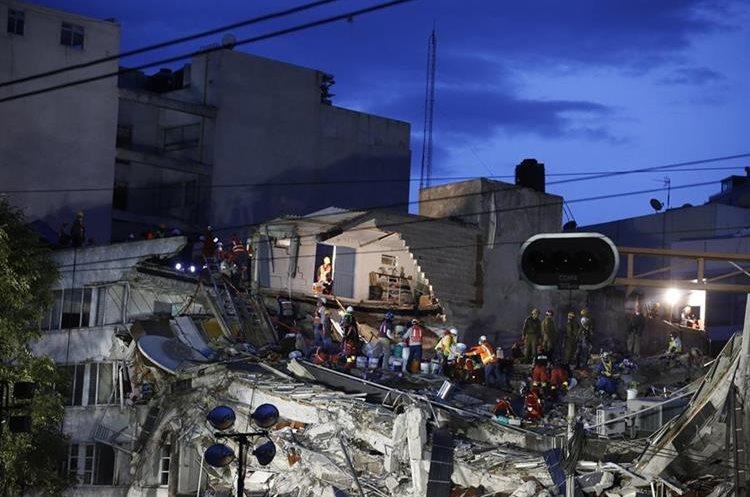 Bescatistas buscan a vítimas mortales en un edificio colapsado en el barrio Roma Norte. (AP).