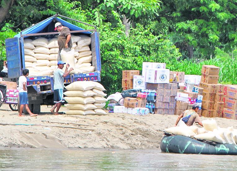 En la frontera Tecún Umán, San Marcos, dos hombres cargan un camión con maíz y articulos mexicanos de contrabando. (Foto Prensa Libre: Hemeroteca PL)
