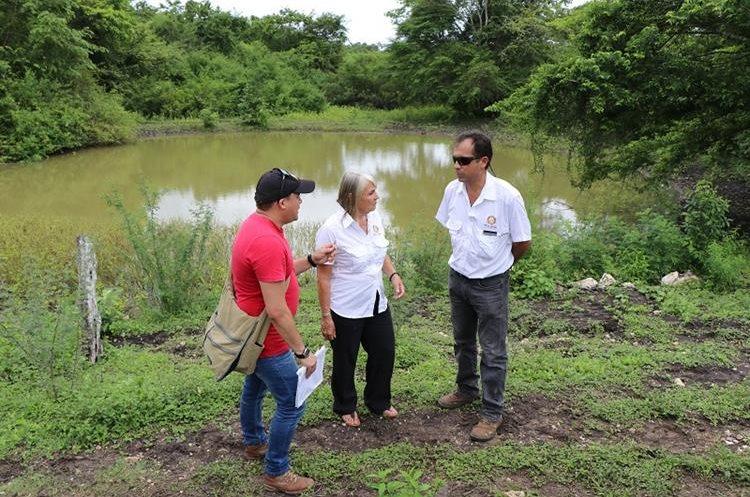 Representantes del Club Rotario conversan cerca de una laguneta de donde los vecinos de Carmelita se abastecían para consumo e higiene personal. (Foto Prensa Libre: Rigoberto Escobar)