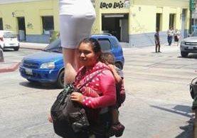 Juana Velásquez carga un maniquí para exhibir los trajes para dama que vende en la zona 1 capitalina. (Foto Prensa Libre: Edwin Pitán)