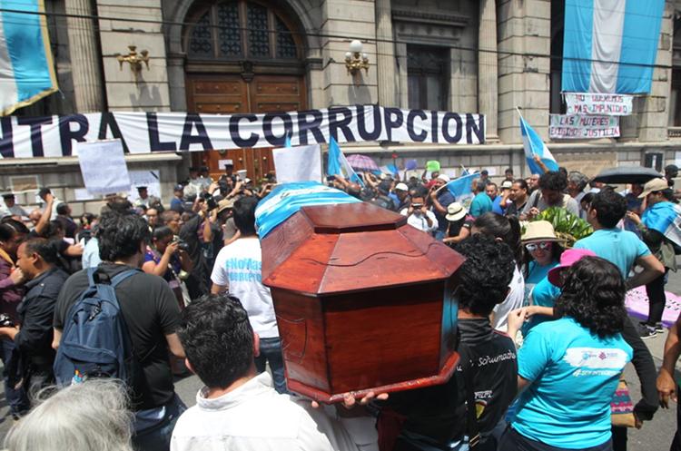 Manifestantes cargan un ataúd como señal de repudio hacia el Congreso. (Foto Prensa Libre: Érick Ávila)