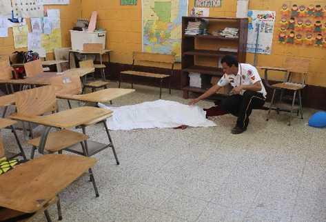 Un bombero Voluntario cubre el cuerpo de Juan Armando Coy Caal, de 13 años, que yace en el salón de tercero primaria, donde estudiaba.