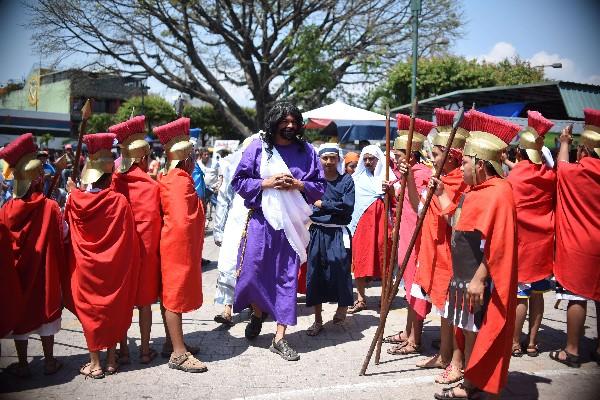 Actores dan vida a la Pasión de Jesús, en un viacrucis que se realiza en Villa Nueva. (Foto Prensa Libre: AFP)