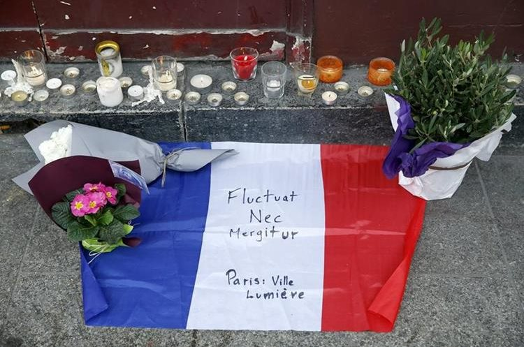 VAL111. Paris (France), 14/11/2015.- Flowers, candles and a French flag are display in front of the Carillon cafe restaurant in Paris, France, 14 November 2015. At least 120 people have been killed in a series of attacks in Paris on 13 November, according to French officials. Eight assailants were killed, seven when they detonated their explosive belts, and one when he was shot by officers, police said. French President Francois Hollande says that the attacks in Paris were an
