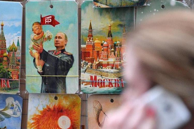 Un quiosco de recuerdos exhibe un dibujo de Putin sosteniendo a un bebé con la cara de Trump en Moscú. (AFP).
