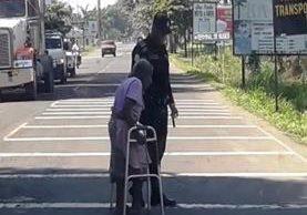 Uno de los agentes ayuda a la anciana de 77 años a cruzar la carretera, en la entrada a Tecún Umán, San Marcos. (Foto Prensa Libre: cortesía)