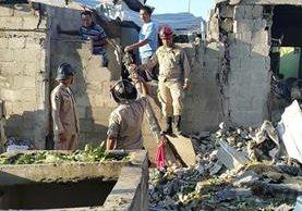 Bomberos de Honduras trabajan en medio de las viviendas afectadas por la explosión. (Foto Prensa Libre: EFE).