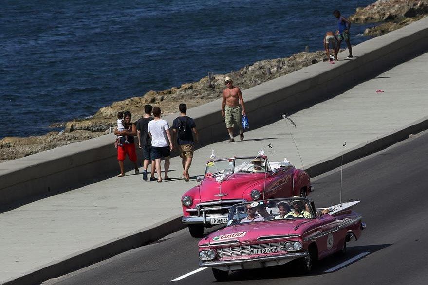 Turistas viajan en un viejo descapotable del pasado siglo por el malecón de La Habana. (Foto Prensa Libre: EFE).
