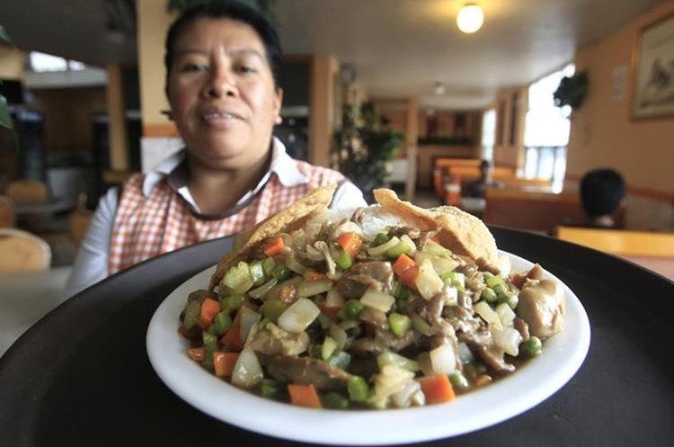 Cristi López muestra uno de los platillos que ofrecen en el restaurante de comida china El Pegaso. (Foto Prensa Libre: Carlos Hernández).