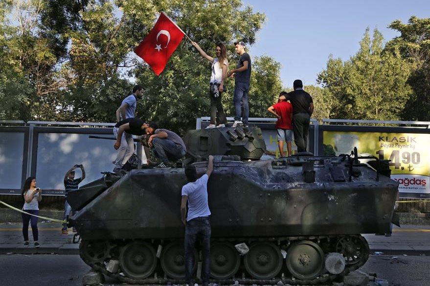 Hombres en Estambul celebran la frustración del golpe sobre un tanque del Ejército. (Foto Prensa Libre: AP).
