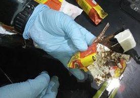 Agentes antinarcóticos de la PNC efectúan pruebas a narcóticos hallados en el Aeropuerto Internacional La Aurora. (Foto Prensa Libre: PNC)
