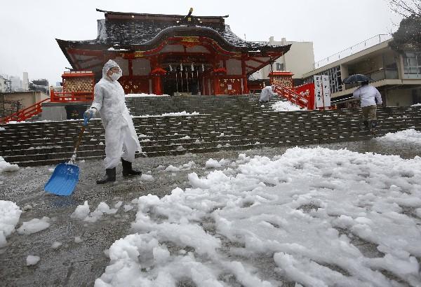 Varios trabajadores limpian la nieve en el Santuario Hanazono, en Tokio, Japón.