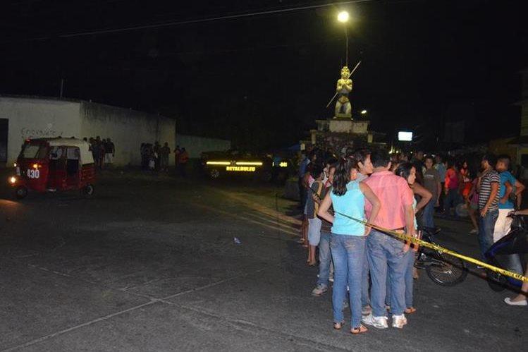 Curiosos observan el lugar donde quedó la unidad 430, donde fue atacado por sicarios el segundo mototaxista en menos de una semana en Retalhuleu. (Foto Prensa Libre: Jorge Tizol).