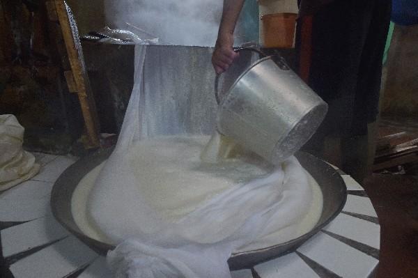 Un trabajador bate la leche de soya y escurre los residuos y sacan el tofu.
