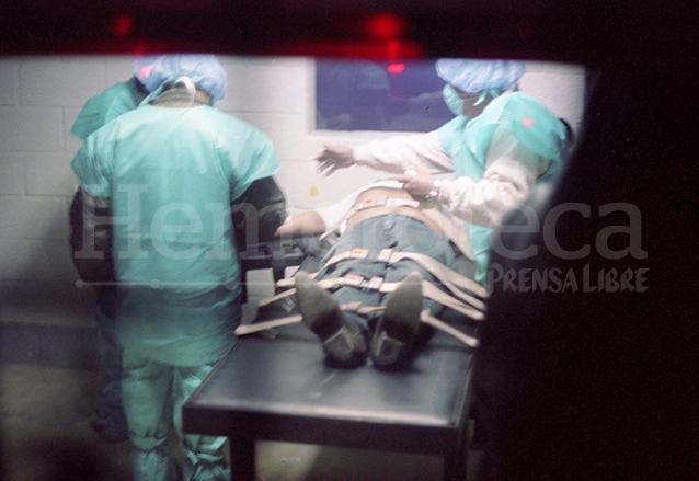 Paramédicos proceden a retirar la jeringa utilizada para aplicar la dosis mortal al reo Manuel Martínez Coronado el 10/2/1998. (Foto: Hemeroteca PL)