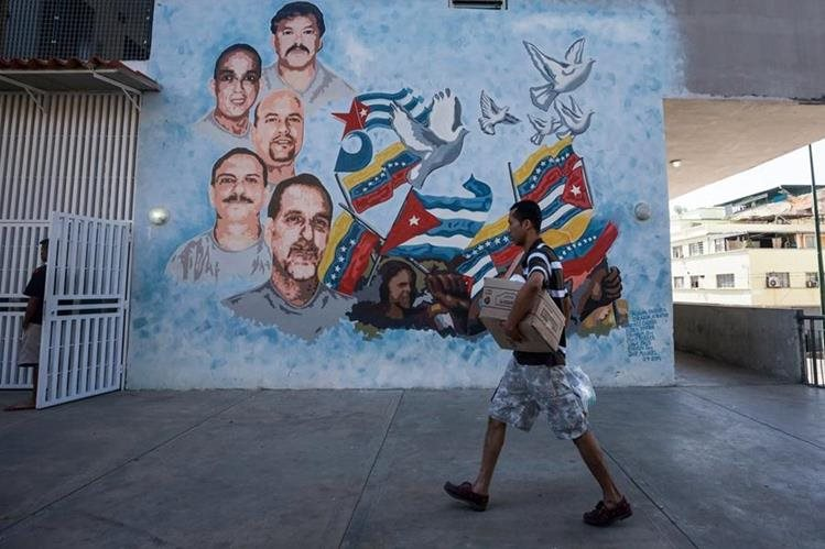 Un hombre camina cargando una caja de alimentos que compró en un programa gubernamental; el país afronta una crisis económica grave. (Foto Prensa Libre: EFE).