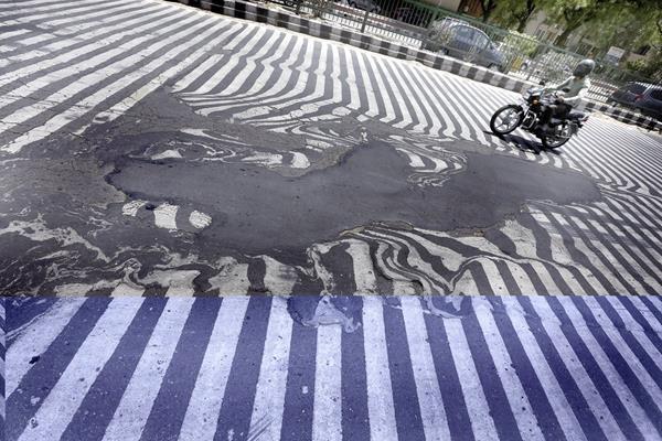 Un vendedor se protege del Sol y el calor en Gurgaon, Nueva Delhi. (Foto Prensa Libre: AFP).