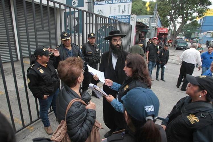 Fiscales del MP muestran la orden de allanamiento para ingresar a las viviendas de la comunidad judía en la zona 9. (Foto Prensa Libre: Erick Ávila)