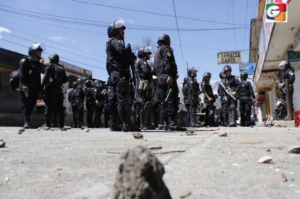La turba lanza piedras a los agentes de la PNC que tratan de dispersar a los pobladores. (Foto Prensa Libre: Guatevisión)