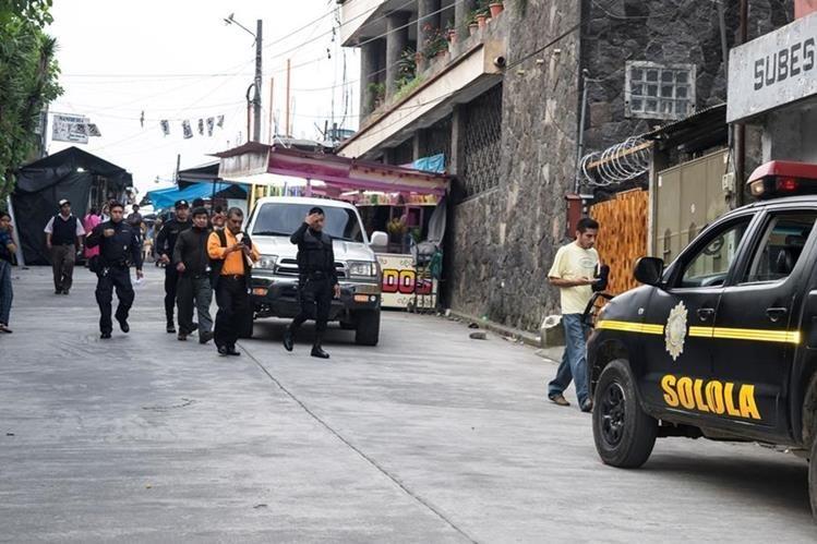 Agentes de la PNC custodian a dos capturados de la comuna de San Lucas Tolimán, Sololá, el lunes último. (Foto Prensa Libre: cortesía de José Cerezo)
