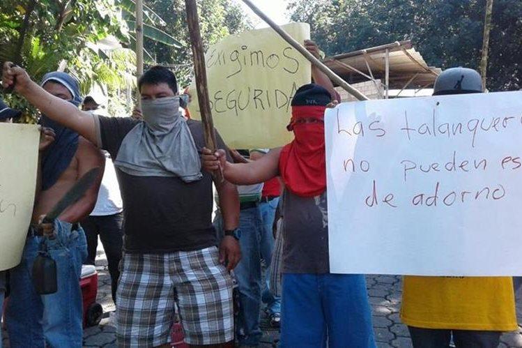 Pilotos de mototaxis en Chicacao muestran pancartas en las que exigen seguridad a las autoridades. (Foto Prensa Libre: Melvin J. Popá)