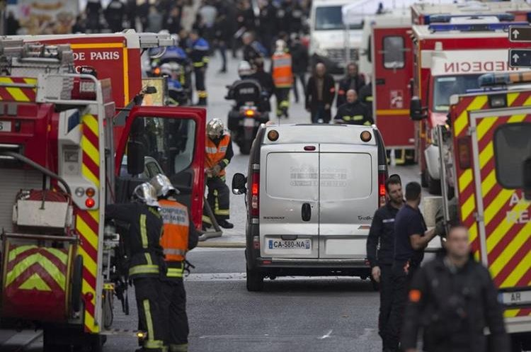 A hearse, center, arrives after an intervention of security forces against a group of extremists in Saint-Denis, near Paris, Wednesday, Nov. 18, 2015. A woman wearing an explosive suicide vest blew herself up Wednesday as heavily armed police tried to storm a suburban Paris apartment where the suspected mastermind of last week