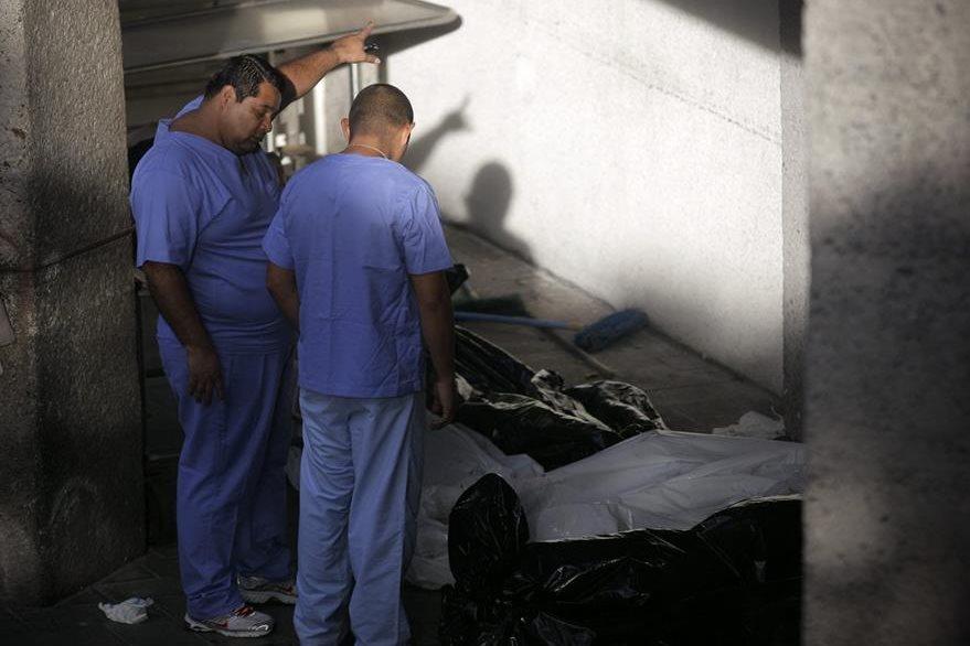 Técnicos forenses observan varios cadáveres que permanecen en una morgue en Santa Tecla. (Foto Prensa Libre: EFE).