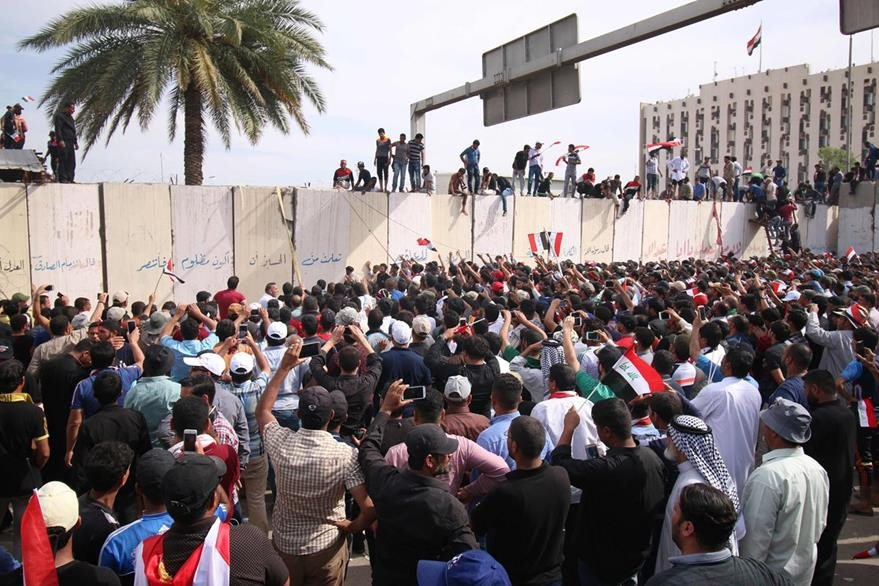 Iraqi protesters climb over a concrete wall surrounding the parliament (unseen) after breaking into Baghdad