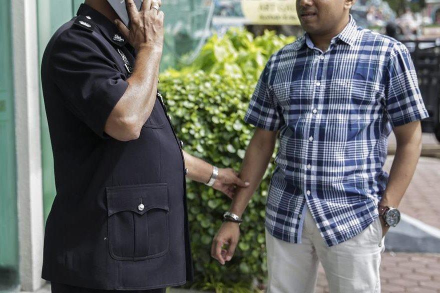 Un policía no identificado (izquierda), habla por teléfono en Malasia. (Foto Prensa Libre: EFE).