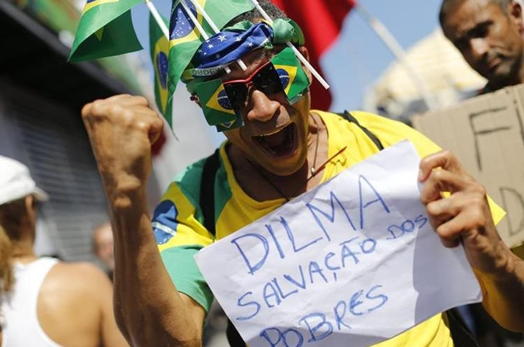 "A man holds a sign that reads in Portuguese ""Dilma is the salvation of the poor"" during a protest against the impeachment of Brazil"