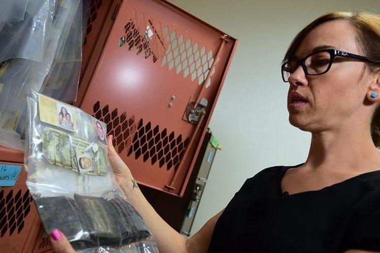 Robin Reineke, la antropóloga que recolecta pertenencias de inmigrantes fallecidos, muestra una bolsa que fotos y dinero que alguien dejó en el desierto. (Foto Prensa Libre: AFP).