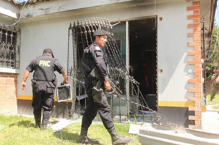Agentes de la PNC de Santa Eulalia, Huehutenango,limpian subestación que destrozó turba. (Foto Prensa Libre: Mike Castillo)
