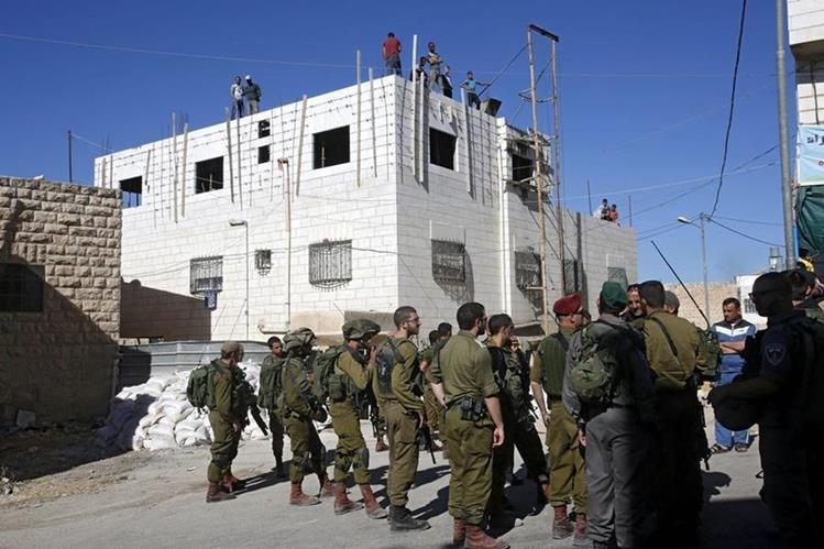 Soldados israelíes rodean una vivienda en construcción mientras se disponen a detener los trabajos de los obreros en la ciudad cisjordana de Hebrón en Palestina. (Foto Prensa Libre: EFE)