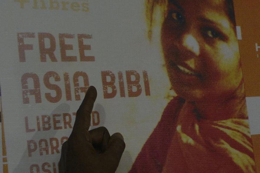 Ashiq Masih, esposo de Asia Bibi, señala un poster propagandístico en donde se pide la liberación de Bibi. (Foto Prensa Libre: AFP).