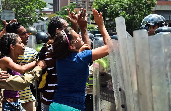 Manifestante y  fuerzas de seguridad  se enfrentan en Caracas, Venezuela. (AFP).