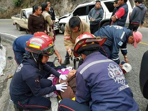 Bomberos atienden a una de las personas heridas luego del percance. (Foto Prensa Libre: Héctor Cordero)
